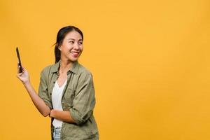 jovem asiática usando telefone com expressão positiva, sorri amplamente, vestida com roupas casuais, sentindo felicidade e carrinho isolado em fundo amarelo. feliz adorável feliz mulher alegra sucesso. foto
