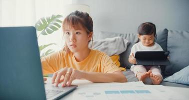 feliz alegre mãe de família Ásia usando laptop com seu filho segurar o desenho animado interesse tablet no sofá enquanto trabalhava em casa na sala de estar. distanciamento social, quarentena para prevenção de coronavírus. foto