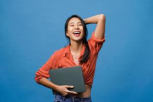 surpresa jovem asiática segurar laptop com expressão positiva, sorriso amplo, vestido com roupas casuais e olhando para a câmera sobre fundo azul. feliz adorável feliz mulher alegra sucesso. foto