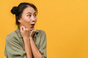 jovem asiática sente felicidade com uma expressão positiva, alegre surpresa funky, vestida com um pano casual, isolado no fundo amarelo. feliz adorável feliz mulher alegra sucesso. expressão facial. foto