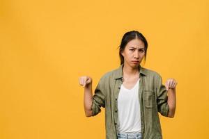 jovem asiática mostra algo incrível no espaço em branco com expressão negativa, animado gritando, chorando emocional com raiva olhando para a câmera isolada sobre fundo amarelo. conceito de expressão facial. foto