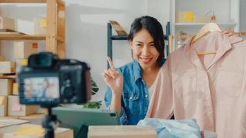 jovem estilista da Ásia usando o telefone celular, recebendo o pedido de compra e mostrando as roupas, gravando vídeo com transmissão ao vivo online com a câmera. proprietário de uma pequena empresa, conceito de entrega de mercado online. foto