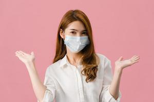 jovem asiática usando máscara médica mostrando o símbolo da paz, incentive com vestido de pano casual e olhando para a câmera isolada no fundo rosa. distanciamento social, quarentena para o vírus corona. foto