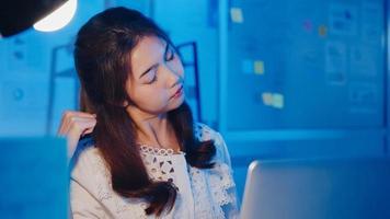 Estressada cansada jovem asiática usando trabalho duro do laptop com síndrome do escritório, dor de garganta durante as horas extras no escritório. trabalhando em casa com sobrecarga à noite, distanciamento social para o vírus corona. foto
