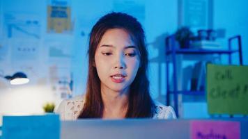 Ásia empresária distanciamento social em novo normal para prevenção de vírus, olhando para a apresentação da câmera para um colega sobre o plano de videochamada enquanto trabalha no escritório à noite. estilo de vida após o coronavírus. foto