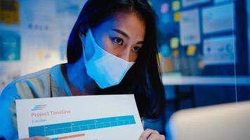Ásia empresária distanciamento social em nova situação normal para prevenção ao usar laptop apresentação para colegas sobre plano em videochamada enquanto trabalho no escritório à noite. vida após o vírus corona. foto