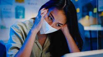 mulheres asiáticas freelance usam máscara facial usando trabalho duro do laptop no novo escritório normal. sobrecarga noturna de trabalho em casa, auto-isolamento, distanciamento social, quarentena para prevenção do vírus corona. foto