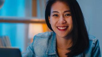 alegre jovem designer gráfico usando tablet gráfico digital enquanto trabalhava até tarde em um escritório moderno à noite, asiática mulher profissional usando retocador de computador laptop sentado na sala de estar em casa. foto