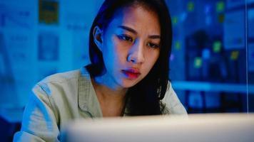 mulheres asiáticas freelance usando laptop trabalham duro no novo escritório normal. trabalhar em casa sobrecarga à noite, trabalhar remotamente, auto-isolamento, distanciamento social, quarentena para prevenção do vírus corona. foto