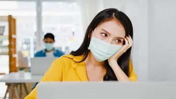 mulheres asiáticas freelance usam máscara facial usando trabalho duro do laptop no novo escritório doméstico normal. trabalhando a partir da sobrecarga da casa, auto-isolamento, distanciamento social, quarentena para prevenção do vírus corona. foto