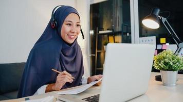 ásia senhora muçulmana usar fone de ouvido assistir webinar ouvir curso online comunicar-se por videoconferência à noite home office. trabalhar remotamente de casa, distância social, quarentena para o vírus corona. foto