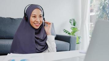 A senhora muçulmana asiática usa fone de ouvido usando o laptop e fala com colegas sobre o plano em uma videoconferência enquanto trabalha em casa na sala de estar. distanciamento social, quarentena para prevenção do vírus corona. foto
