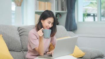 mulher asiática freelance jovem negócios trabalhando no laptop, verificando as mídias sociais e bebendo café enquanto estava deitado no sofá quando relaxava na sala de estar em casa. mulheres de estilo de vida no conceito de casa. foto