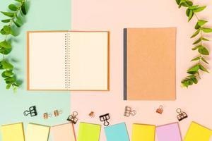 foto plana leiga criativa da mesa do espaço de trabalho. mesa de escritório com vista superior com nota adesiva e caderno preto de maquete aberta sobre fundo de cor rosa verde pastel. vista superior simulada com fotografia do espaço da cópia.