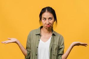 retrato de uma jovem senhora asiática com expressão negativa, animado, gritando, chorando com raiva emocional em roupas casuais, isolado em um fundo amarelo com espaço de cópia em branco. conceito de expressão facial. foto