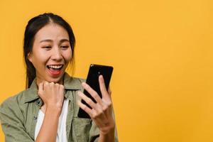 surpreendeu a jovem asiática usando telefone celular com expressão positiva, sorri amplamente, vestida com roupas casuais e carrinho isolado em fundo amarelo. feliz adorável feliz mulher alegra sucesso. foto