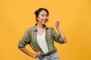 retrato de uma jovem senhora asiática, sorrindo com uma expressão alegre, mostra algo incrível no espaço em branco em roupas casuais e em pé isolado sobre fundo amarelo. conceito de expressão facial. foto