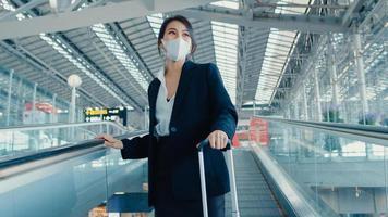 garota de negócios asiáticos usar máscara facial arraste carrinho de bagagem na escada rolante olhar ao redor caminhar para o terminal no aeroporto internacional. pandemia de covid de viajante de negócios, conceito de distanciamento social de viagens de negócios. foto