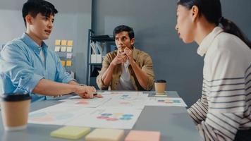 jovens empresários e mulheres de negócios asiáticos felizes reunindo-se e debatendo algumas novas idéias sobre o projeto para seu parceiro, trabalhando juntos, planejando uma estratégia de sucesso, desfrute do trabalho em equipe em um pequeno e moderno escritório em casa. foto