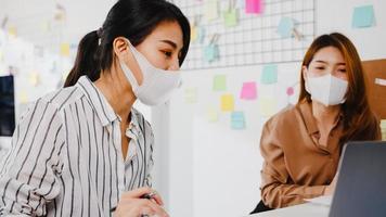 empresários asiáticos usando apresentação de computador, reunindo-se para debater ideias sobre novos colegas de projeto e usando máscara protetora no novo escritório normal. estilo de vida e trabalho após coronavírus. foto