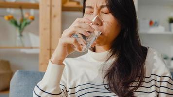 mulher asiática jovem doente segurando um copo de comprimido de água tomar remédio sentar no sofá em casa. garota tomando remédio após ordem do médico, quarentena em casa, conceito de quarentena de distanciamento social do coronavirus. foto