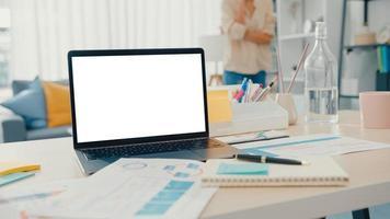 computador portátil com simulação de tela branca em branco para texto de publicidade na mesa na sala de estar em casa moderna. tecnologia chroma key, conceito de design de marketing. foto