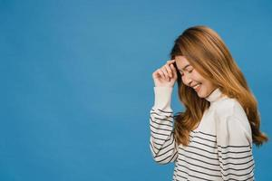retrato de uma jovem senhora asiática com expressão positiva, sorriso amplo, vestida com roupas casuais sobre fundo azul. feliz adorável feliz mulher alegra sucesso. conceito de expressão facial. foto