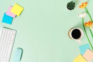 espaço de trabalho mínimo - foto criativa plana da mesa do espaço de trabalho. mesa de escritório de vista superior com teclado e mouse sobre fundo de cor verde pastel. vista superior com espaço de cópia, fotografia plana leiga.
