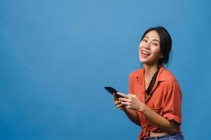 surpreendeu a jovem asiática usando telefone celular com expressão positiva, sorria amplamente, vestida com roupas casuais e olhando para a câmera sobre fundo azul. feliz adorável feliz mulher alegra sucesso. foto