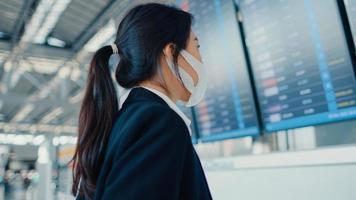 garota de negócios asiáticos usar máscara facial com mala em frente a placa olhar para informações, verificando seu voo no aeroporto internacional. pandemia de covid de viajante de negócios, conceito de viagens de negócios. foto