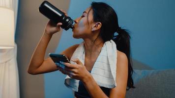 jovem asiática usando telefone celular e bebendo água pura no sofá na sala de estar em casa à noite. atividade de esporte e recreação, distanciamento social, quarentena para o conceito de prevenção do vírus corona. foto