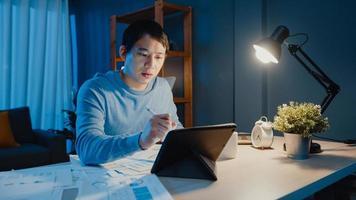 ásia empresário freelance foco trabalho caneta escrever no computador tablet ocupado com cheio de papelada gráfica na mesa na sala de estar em casa horas extras à noite, trabalhar em casa durante o conceito de pandemia covid-19. foto