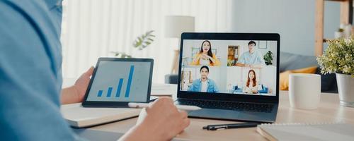 jovem empresário asiático usando laptop fala com colegas sobre o plano de videochamada reunião trabalho de casa na sala de estar. auto-isolamento, distância social, fundo de banner panorâmico com espaço de cópia. foto