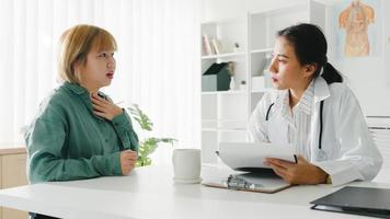 jovem médica asiática em uniforme médico branco, usando a área de transferência, está entregando grandes notícias, discute os resultados ou sintomas com uma paciente sentada à mesa na clínica de saúde ou no escritório do hospital. foto