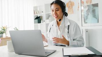 jovem doutora da Ásia em uniforme médico branco com estetoscópio, usando o computador laptop, falando por videoconferência com o paciente na mesa na clínica de saúde ou hospital. consultoria e conceito de terapia. foto