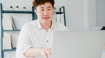 jovem empresário asiático usando laptop fala com colegas sobre o plano de videochamada enquanto inteligente trabalhando em casa na sala de estar. auto-isolamento, distanciamento social, quarentena para prevenção do vírus corona. foto