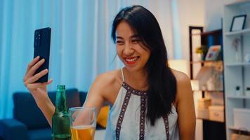jovem asiática bebendo cerveja se divertindo momento feliz noite festa ano novo evento on-line celebração via videochamada por telefone em casa à noite. distanciamento social, quarentena para prevenção de coronavírus. foto