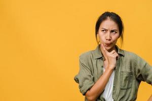 retrato de uma jovem senhora asiática com expressão positiva, pensa nas próximas férias, vestida com roupas casuais, sobre fundo amarelo com espaço de cópia em branco. feliz adorável feliz mulher alegra sucesso. foto