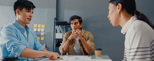 jovens empresários da ásia reunindo-se para debater algumas novas idéias sobre projeto para parceria, trabalho conjunto, plano de estratégia de sucesso, trabalho em equipe no escritório. fundo de banner panorâmico com espaço de cópia. foto