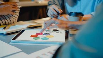 os empresários da ásia reunindo-se com o brainstorm de estatísticas de análise de plano e o cabeçalho da equipe seguram o gráfico do gráfico de pontos do tablet e o funcionário toma nota na noite do escritório em casa moderno. conceito de sucesso de estratégia de finanças. foto