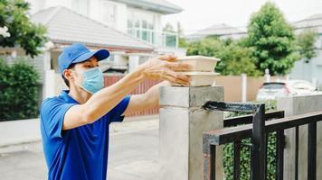 jovem mensageiro de entrega postal usa máscara facial manuseando caixa de comida para enviar ao cliente em casa e mulher asiática recebe pacote entregue ao ar livre. estilo de vida novo normal após o conceito de vírus corona. foto