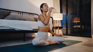 jovem asiática fazendo exercícios de ioga malhando e bebendo água pura na sala de estar em casa à noite. atividade de esporte e recreação, distanciamento social, quarentena para o conceito de prevenção do vírus corona. foto
