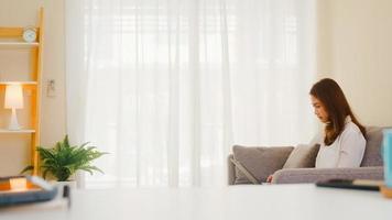 retrato de roupas casuais de mulheres asiáticas freelance usando laptop, trabalhando na sala de estar em casa. trabalhar em casa, trabalhar remotamente, auto-isolamento, distanciamento social, quarentena para prevenção de coronavírus. foto