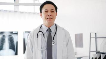 jovem médico asiático em uniforme médico branco com estetoscópio olhando para a câmera, sorriso e braços cruzados durante a videoconferência com o paciente no hospital de saúde. consultoria e conceito de terapia. foto
