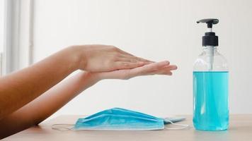 mulher asiática usando álcool gel desinfetante para as mãos, lavar as mãos antes de usar máscara para proteger o coronavírus. mulheres empurram o álcool para limpar para higiene quando o distanciamento social fica em casa e tempo de quarentena. foto
