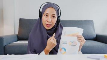A senhora muçulmana da ásia usa fone de ouvido usando o laptop do computador para falar com os colegas sobre o relatório de venda em videochamada enquanto trabalha remotamente em casa na sala de estar. distanciamento social, quarentena para o vírus corona. foto