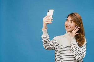 sorrindo adorável mulher asiática fazendo foto de selfie no telefone inteligente com expressão positiva em roupas casuais e ficar isolado sobre fundo azul. feliz adorável feliz mulher alegra sucesso.