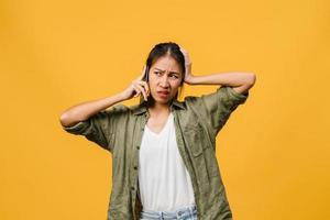 jovem asiática fala por telefone com expressão negativa, gritando animado, chora com raiva emocional em um pano casual e fica isolado em um fundo amarelo com espaço de cópia em branco. conceito de expressão facial. foto