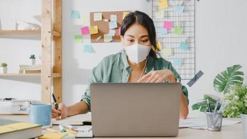 empresária asiática usando máscara médica usando laptop fala com colegas sobre o plano de videochamada enquanto trabalha em casa na sala de estar. distanciamento social, quarentena para prevenção do vírus corona. foto