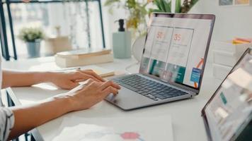 close-up jovem asiática freelance foco no trabalho finanças gráfico conta gráfico plano de mercado no laptop para reunião remota com a empresa em casa. aluna aprender online em casa, trabalhar a partir do conceito de casa. foto